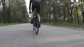Radfahrer, der auf Fahrradabschlu? herauf Beinmuskelansicht radelt Fahrradreiter im Park, der schwarze Sportkleidung tr?gt stock video