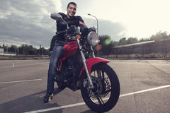 Radfahrer, der auf sportlichem Motorrad sitzt Stockfotos
