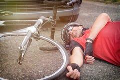 Radfahrer, der auf der Straße nachdem dem Schlagen durch ein Auto liegt Stockfotos