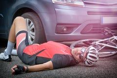Radfahrer, der auf der Straße nachdem dem Schlagen durch ein Auto liegt Stockbilder