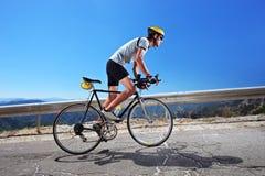Radfahrer, der aufwärts ein Fahrrad reitet Stockbild