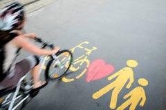 Radfahrer in der Bewegung, die durch das Fußgänger-/Fahrradzeichen überschreitet lizenzfreie stockbilder