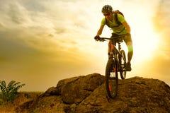 Radfahrer, der das Fahrrad auf Autumn Rocky Trail bei Sonnenuntergang reitet Extremer Sport und radfahrendes Konzept Enduro Stockbilder