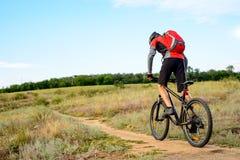 Radfahrer, der das Fahrrad auf den schönen Frühlings-Gebirgspfad reitet Lizenzfreies Stockbild