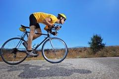 Radfahrer, der ein Fahrrad auf eine geöffnete Straße reitet Lizenzfreies Stockfoto