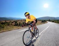 Radfahrer, der ein Fahrrad auf eine geöffnete Straße reitet Lizenzfreies Stockbild