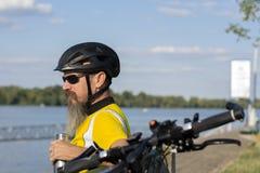 Radfahrer, der eine Pause auf einer Bank nahe Fluss macht lizenzfreie stockfotos