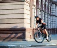 Radfahrer, der historische Gebäude auf Fahrrad führt Stockbild