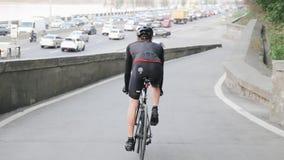 Radfahrer, der in Richtung zur verkehrsreichen Stadtstraße trägt schwarze Sportkleidung absteigt Radfahrenkonzept stock video