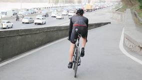 Radfahrer, der in Richtung zur verkehrsreichen Stadtstra?e tr?gt schwarze Sportkleidung absteigt Radfahrenkonzept Langsame Bewegu stock footage