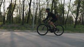 Radfahrer, der schwarzes Trikot tragen und kurze Hosen, die ein schwarzes Berufsrennrad im Park reiten Seite folgen Schuss Radfah stock video footage