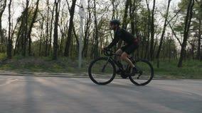 Radfahrer, der schwarzes Trikot tragen und kurze Hosen, die ein schwarzes Berufsrennrad im Park reiten Seite folgen Schuss Radfah stock footage