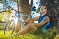 Radfahrer, der unter einem Baum stillsteht Stockfotos