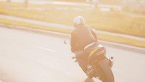 Radfahrer des jungen Mannes im Sonnenuntergang, der ein Motorrad, auf eine Kurve der geasphaltierten Straße mit einem rustikalen  stock video footage