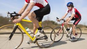 Radfahrer, die auf Landstraße fahren Lizenzfreies Stockfoto