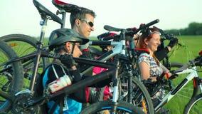 Radfahrer, die Fahrräder durch hohes Gras tragen stock footage