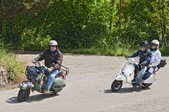 Radfahrer, die italienischen Vespa Roller der Weinlese reiten Lizenzfreies Stockbild