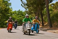 Radfahrer, die italienischen Vespa und Lambretta Roller der Weinlese reiten Lizenzfreie Stockbilder