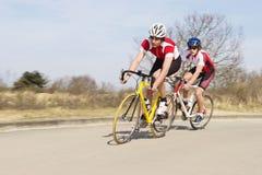 Radfahrer, die Schleifen auf geöffnete Straße reiten Lizenzfreies Stockfoto