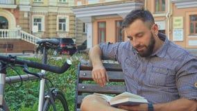 Radfahrer dreht die Seite des Buches auf der Bank stock video footage