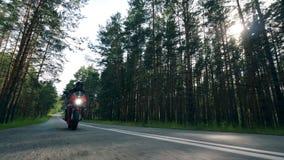 Radfahrer in einem Sturzhelm, der ein Motorrad auf eine Straße reitet stock video footage