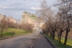 Radfahrer gehen die Andrei Dubensky-Straße der Krasnojarsk-Stadt im Hintergrund eines Wohngebäudes hinauf lizenzfreies stockfoto