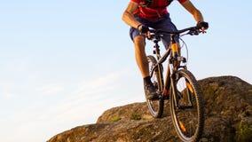 Radfahrer im Rot, welches das Fahrrad hinunter den Felsen auf den blauer Himmel-Hintergrund reitet Extremer Sport und radfahrende lizenzfreies stockfoto
