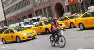 Radfahrer im Verkehr zwischen den gelben Fahrerhäusern in Manhattan, NYC Lizenzfreies Stockfoto