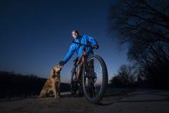 Radfahrer mit einem Hund auf der Flussbank 2017 Lizenzfreie Stockbilder