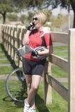 Radfahrer mit ihrem Fahrrad, das auf Zaun bei der Anwendung des Handys sich lehnt Stockbilder