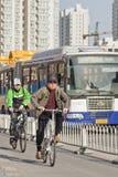Radfahrer in Peking im Stadtzentrum gelegen mit einem Bus auf dem Hintergrund, China Lizenzfreies Stockfoto