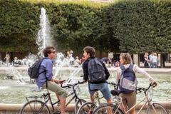 Radfahrer plaudern vor Brunnen im Palais Royal-Garten in P Stockbilder