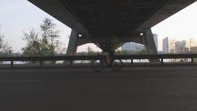 Radfahrer-Schattenbild bei dem Sonnenuntergang, der Fahrrad unter Brücke in der Stadt fährt Fluss und städtische Stadtansicht übe stock video