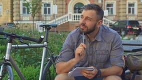 Radfahrer schreibt in sein Notizbuch auf die Bank stock video footage