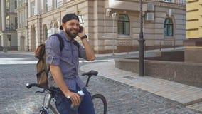 Radfahrer spricht am Telefon auf der Straße stock footage