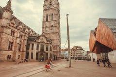 Radfahrer und Fußgänger, die auf alte Straße mit Kirche und modernen Strukturen gehen Stockfotos