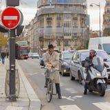 Radfahrer und Motorradfahrer auf einem beschäftigten Schnitt Lizenzfreie Stockbilder