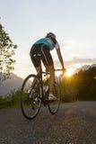 Radfahrer von hinten mit Sonnenuntergang Lizenzfreie Stockfotos