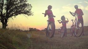 Radfahrerfamilienschattenbild auf dem Feld bei Sonnenuntergang stock footage