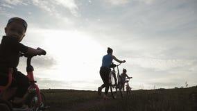 Radfahrerfamilienschattenbild, Eltern mit zwei Kindern auf Fahrr?dern bei Sonnenuntergang Konzept der freundlichen Familie stock footage