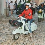 Radfahrerfrau, die einen italienischen Vespa Roller der Weinlese reitet Stockfotografie