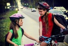 Radfahrerkinderfahrt auf Stadtfahrradweg Mädchen, die Sturzhelm tragen Stockfoto