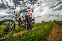 Radfahrermädchen auf einem Motorrad Lizenzfreie Stockfotos