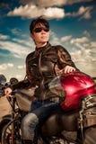 Radfahrermädchen auf einem Motorrad Stockbild