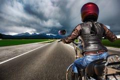 Radfahrermädchen auf einem Motorrad, das hinunter die Straße in einem Blitz rast Lizenzfreies Stockfoto