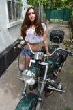 Radfahrermädchen, das auf kundenspezifischem Motorrad der Weinlese sitzt Lebensstil im Freien tonte Porträt lizenzfreies stockbild