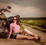 Radfahrermädchen, das auf Motorrad sitzt Stockbild