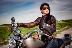 Radfahrermädchen, das auf Motorrad sitzt Stockfotografie