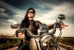 Radfahrermädchen, das auf Motorrad sitzt Lizenzfreies Stockbild