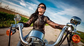 Radfahrermädchen, das auf Motorrad sitzt Stockbilder